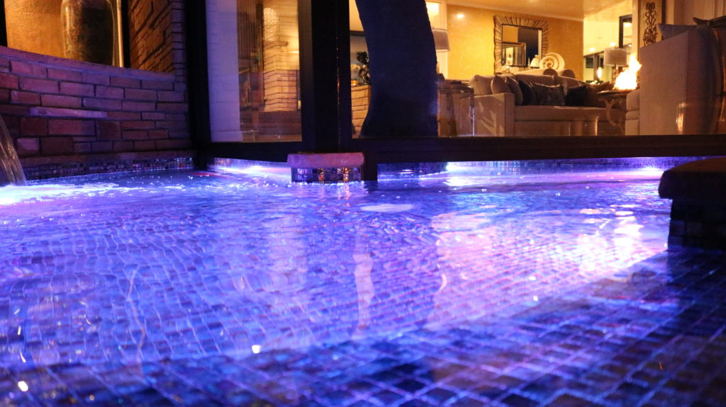 Our House on a Hill project includes a gorgeous display of LED lit water features paired elegantly with fire pit lighting. This is the completion of a backyard renovation project that lasted 6 months from start to finish. This image shows our LED lit water fountain on our raised deck.