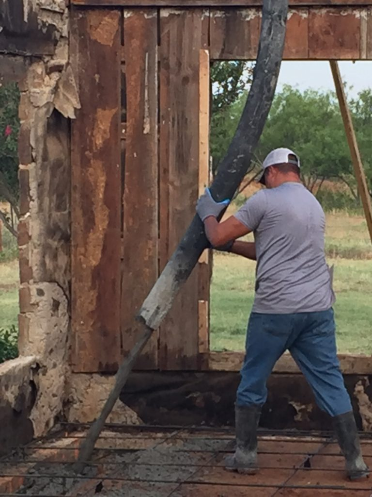Here you can see our crew pouring our concrete slab inside of this home. Wet cement is extremely heavy. Therefore, we station a crane to hold our applicator so we can carefully apply the wet cement to the interior of the home - creating a firm foundation for our client.