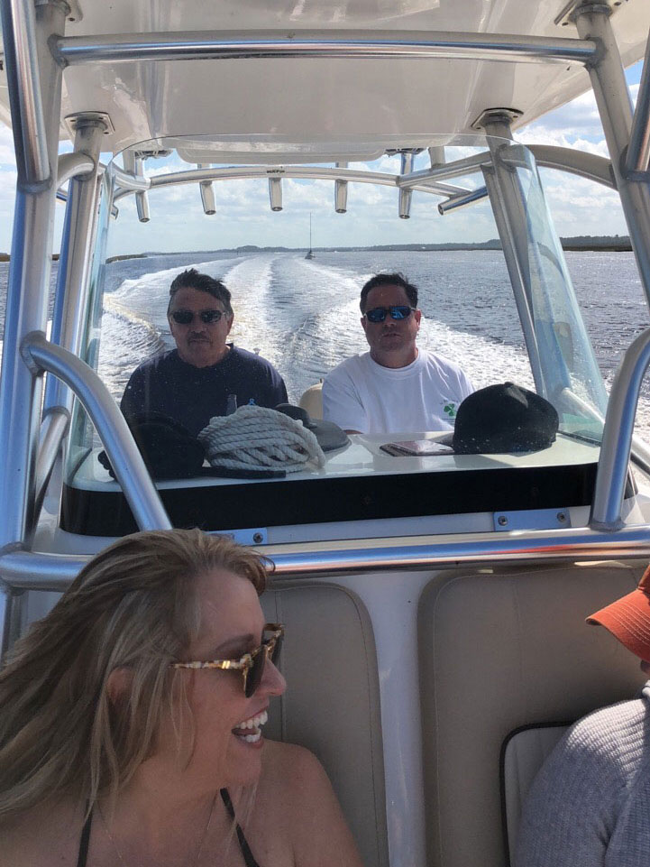 Two men driving a boat with woman laughing the passenger seat
