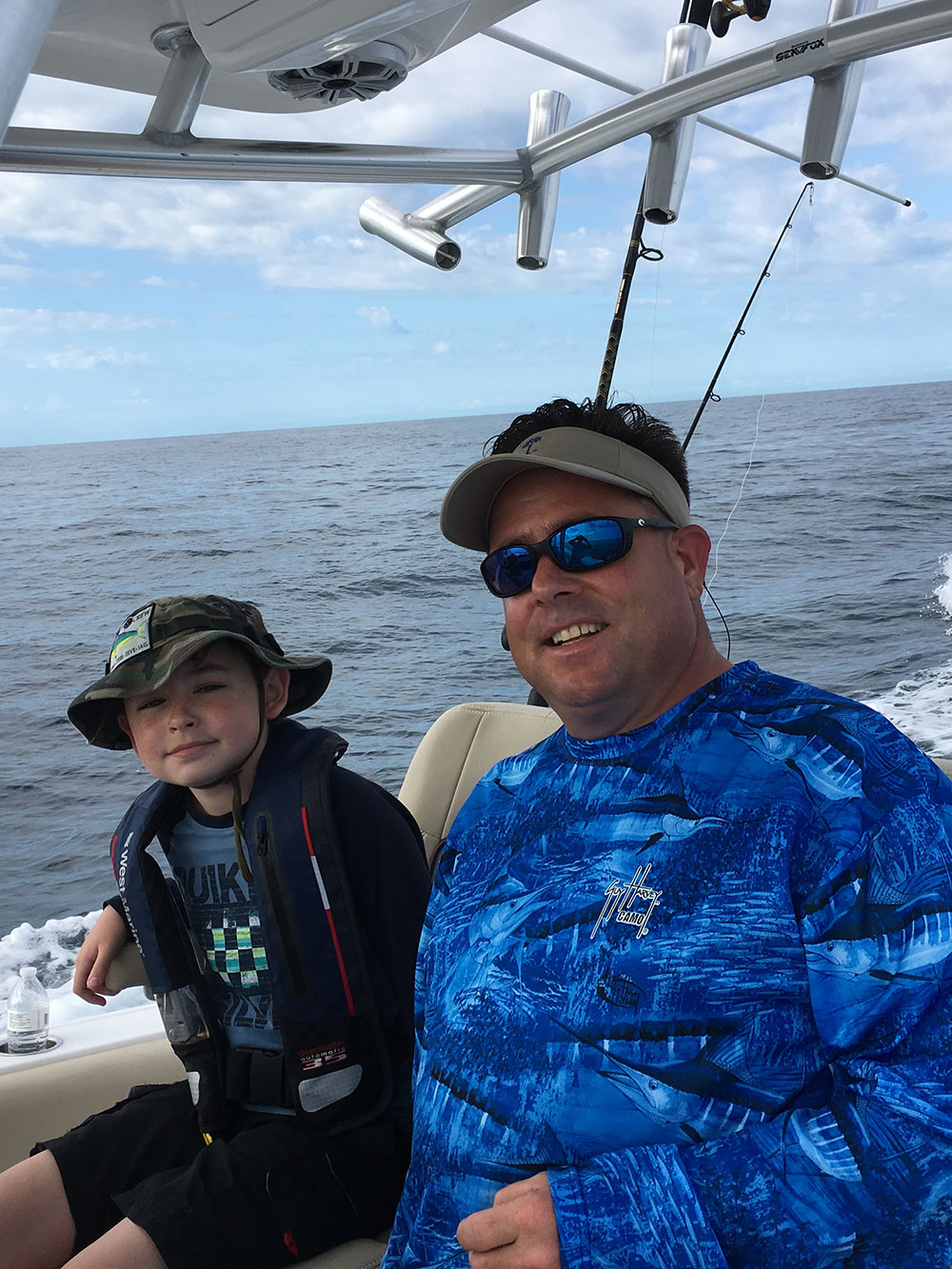 Chris Worth and child sitting on the boat smiling