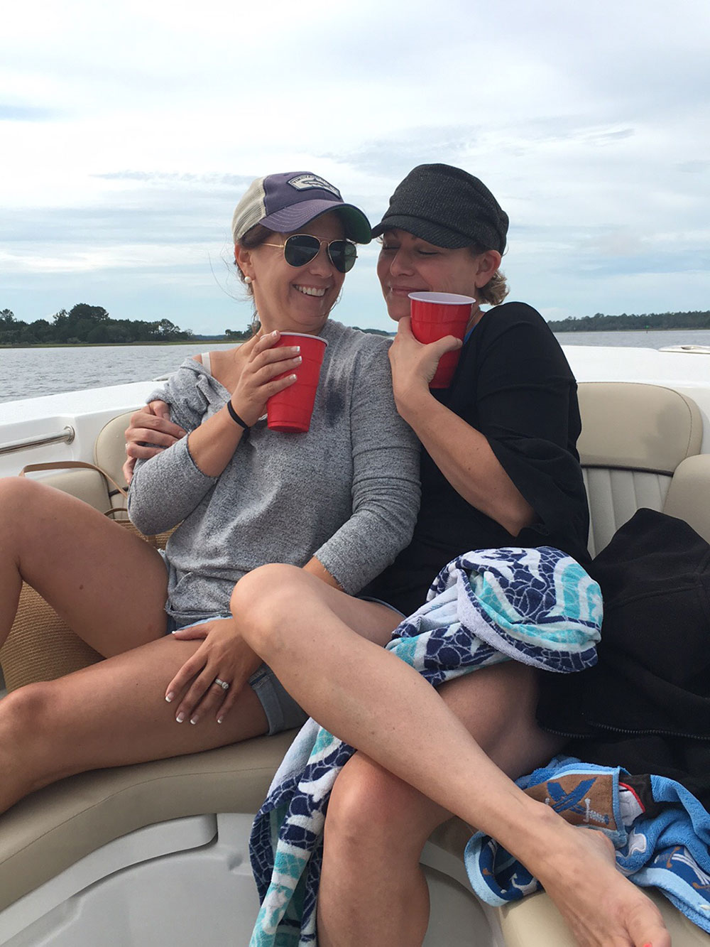 Two women with red plastic drink cups sitting together on a boat