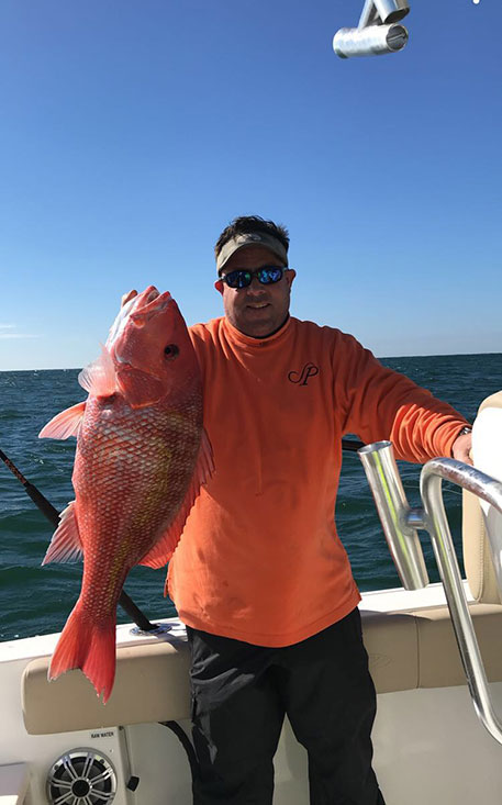 Chris Worth holding a red fish in right hand on a boat