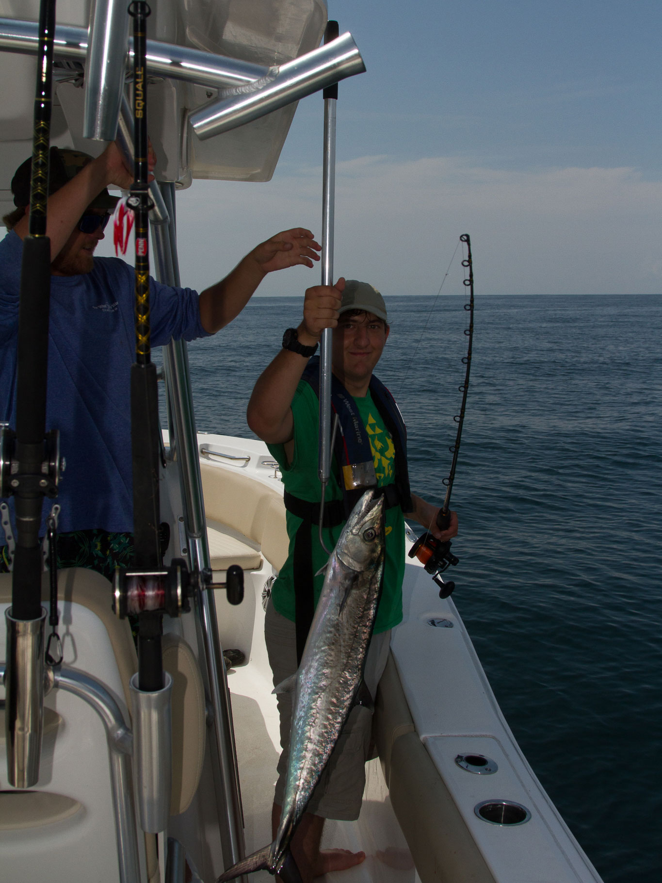man reeling in fish with assistance from the first mate