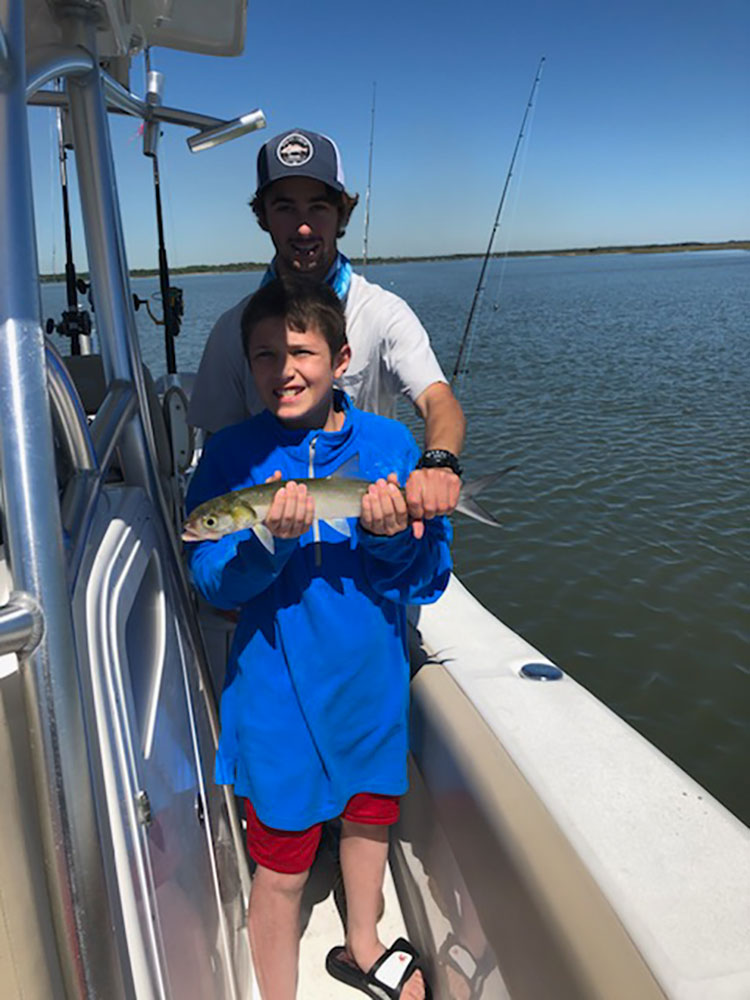 boy and man holding a small fish