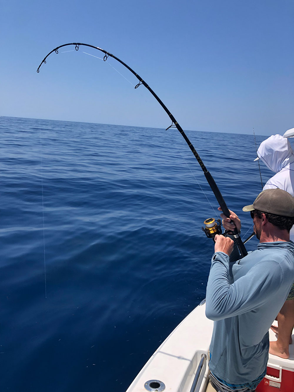 man reeling in a catch