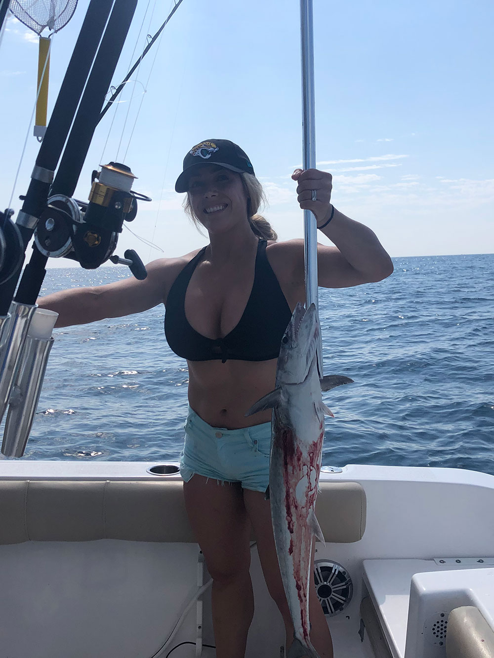 woman holds bloodied fish on the boat