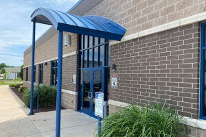 Front door of school with curved blue awning above.