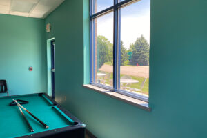 Student lounge pool table and window looking out to green space.