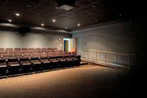 Small theater with rows of chairs and dimmed lighting.