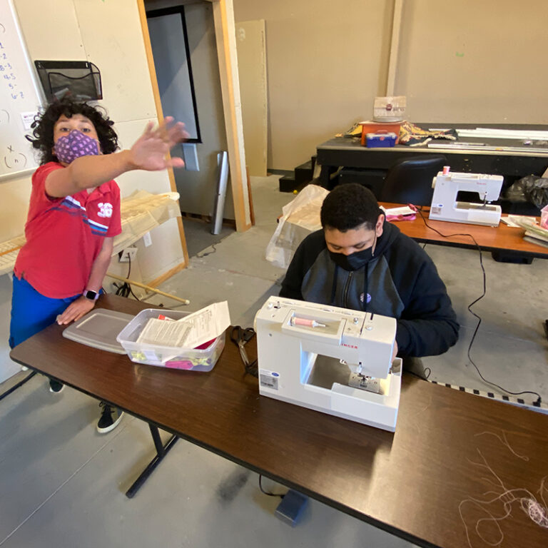 Two students in a sewing class.