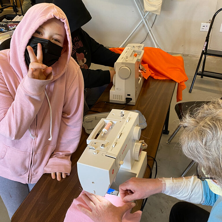 Student in pink hoodie showing a peace sign with her hand as an instructor uses a sewing machine.