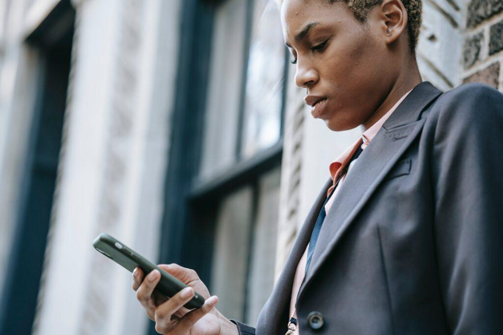 concentrated ethnic businesswoman with smartphone