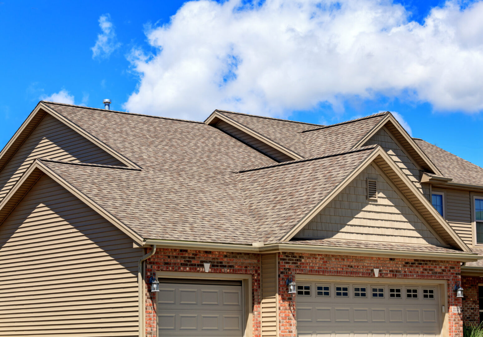 Photo of new asphalt shingles on a two story home. Blue sky and clouds are in the background.