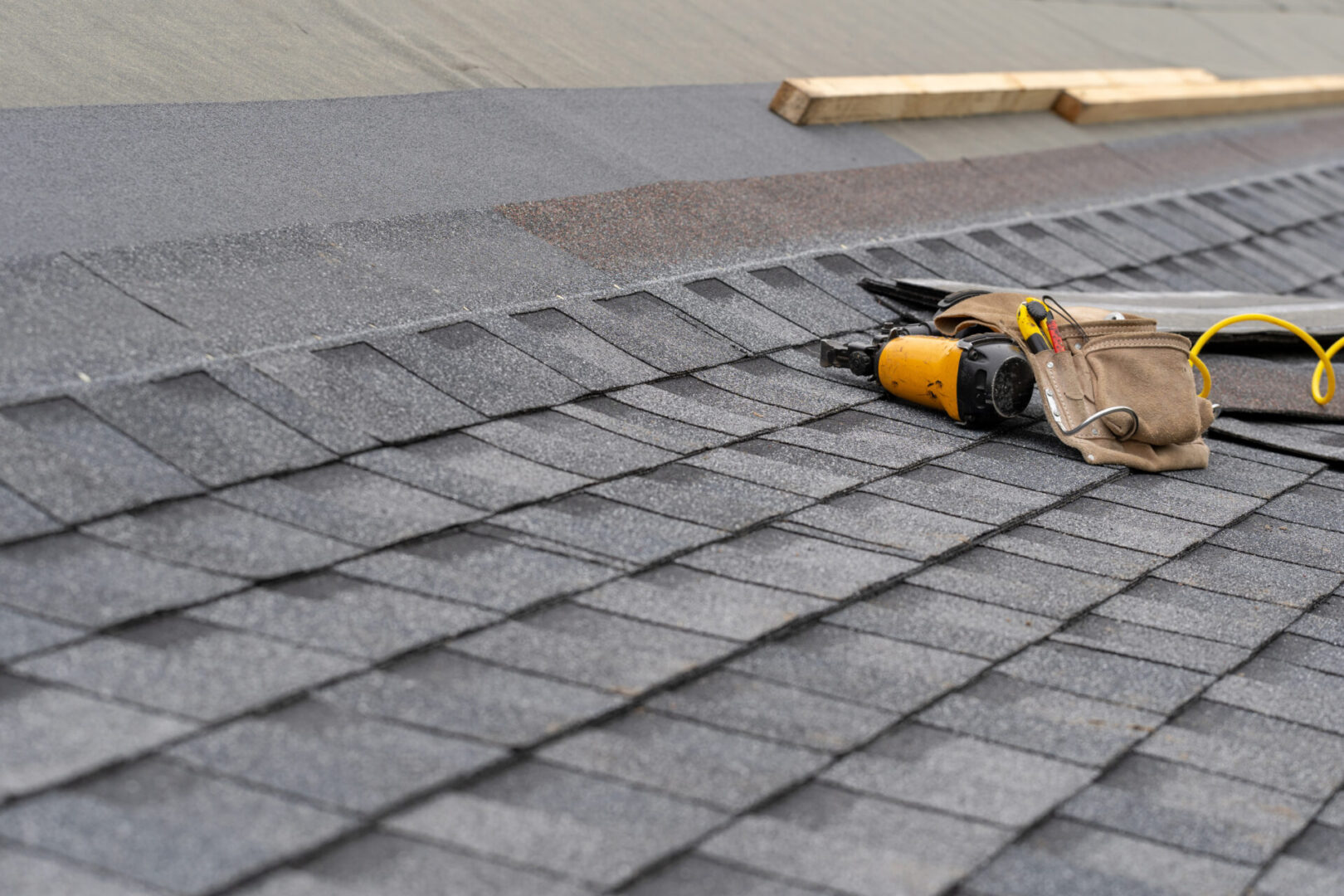 Photo of toolbelt with instrument and nail gun lying on asphalt or bitumen shingle on top of the new roof under construction residential house or building