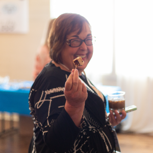 Co-founder Patti Rossman smiling at the camera, holding up a small piece of cake on a fork.