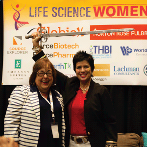 A photo of Cherie Mathews and Patti Rossman, standing proudly in front of the sponsor banner, wielding a broadsword.