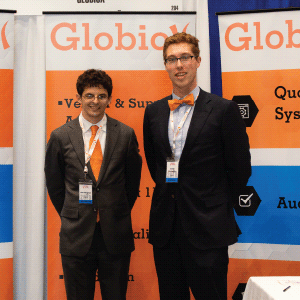 Two Globiox employees representing their sponsor at their booth, speckled with orange, blue and grey.