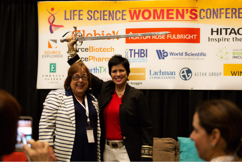 Founder Patti Rossman (left) and Cherie  Mathews (right), opening speaker, wielding a broadsword in front of a sponsor banner onstage. They're smiling, representing the power of the conference.