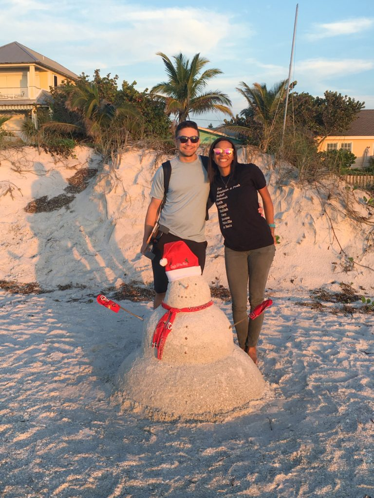 family on a beach with snowman made of sand; holidays