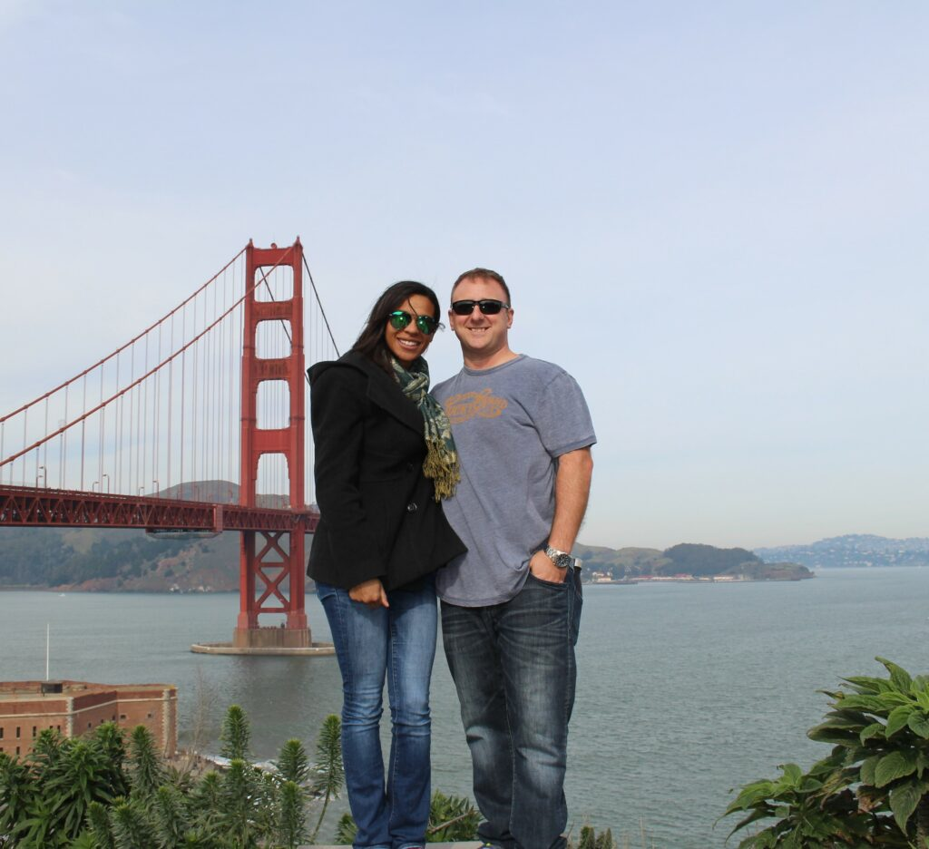couple standing in front of the Golden Gate Bridge