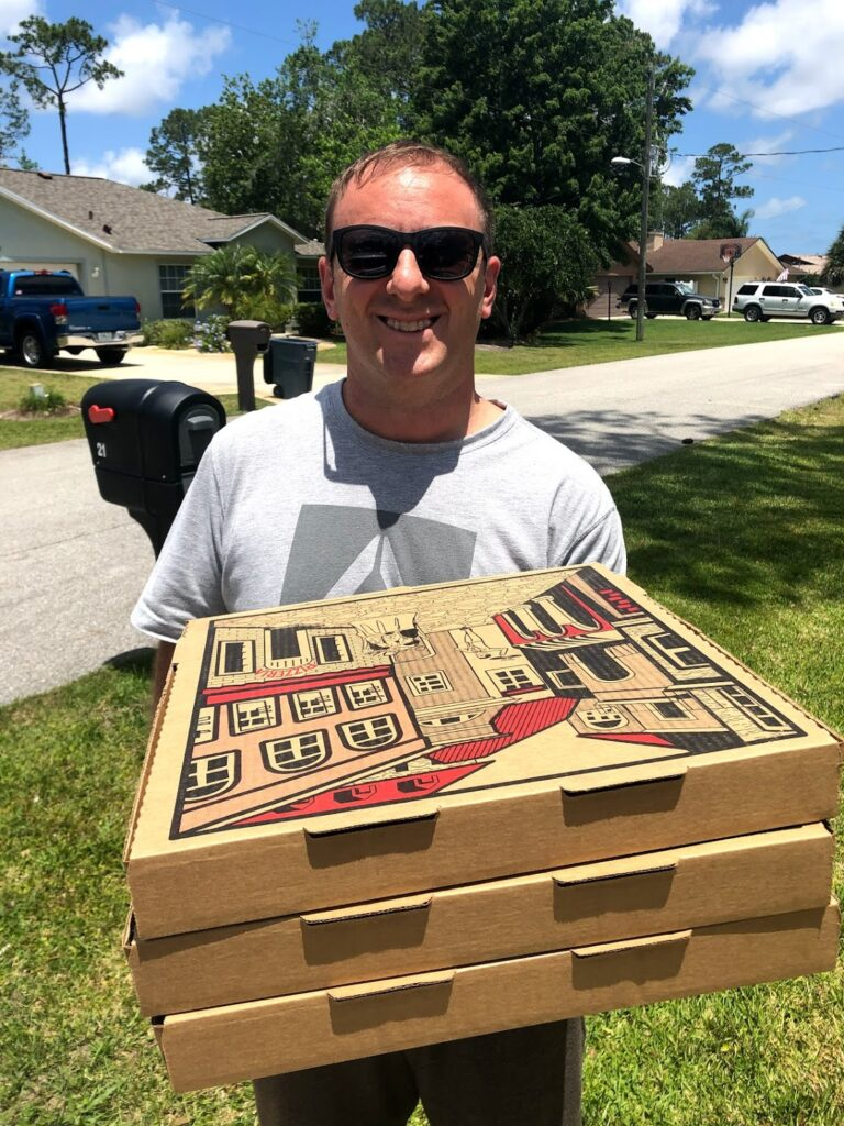 man carrying boxes of pizza