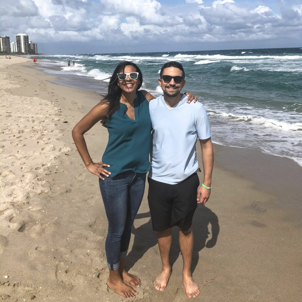a man and woman standing on the beach