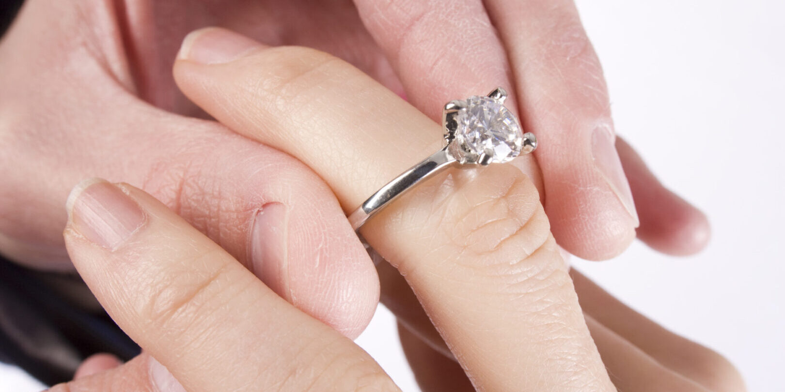 A man slides a diamond ring on his fiance's finger