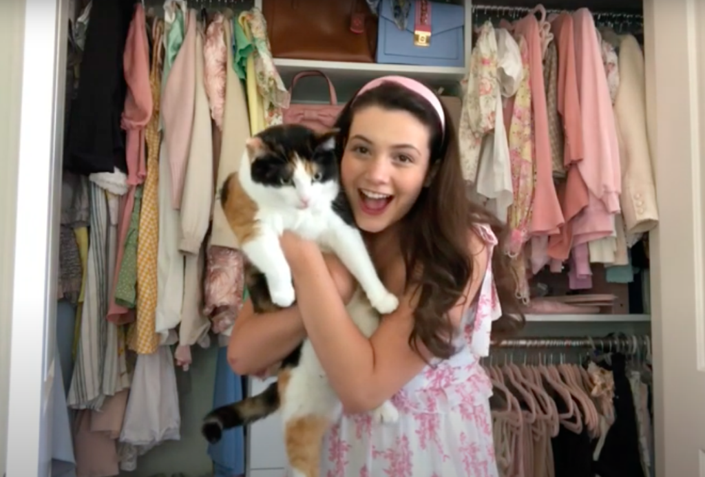 Kaitlyn Riccio youtuber holding her cat in front of her closet which is full of cool pink clothes
