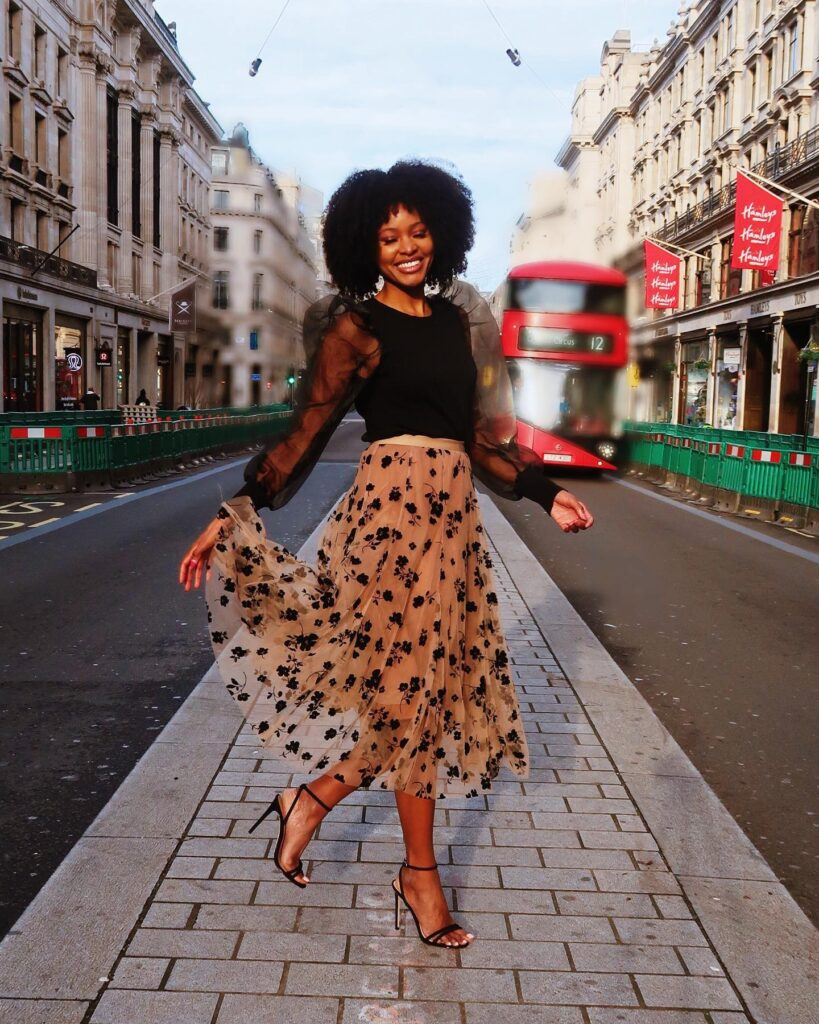 woman wearing a polka dot tulle skirt with a black top with sheer bell sleeves and heels