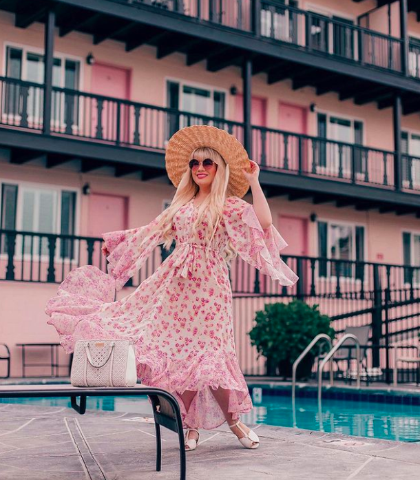 blogger lizzie in lace wearing a floral dress with ruffled cascading sleeves and pink on a white background. She's standing by a pool in front of a pink hotel.