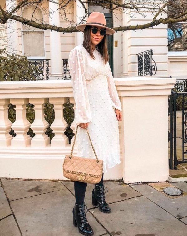 blogger wearing one of the white chicwish dresses which has long sheer bell sleeves with white polka dots on them and an a-line silhoeutte