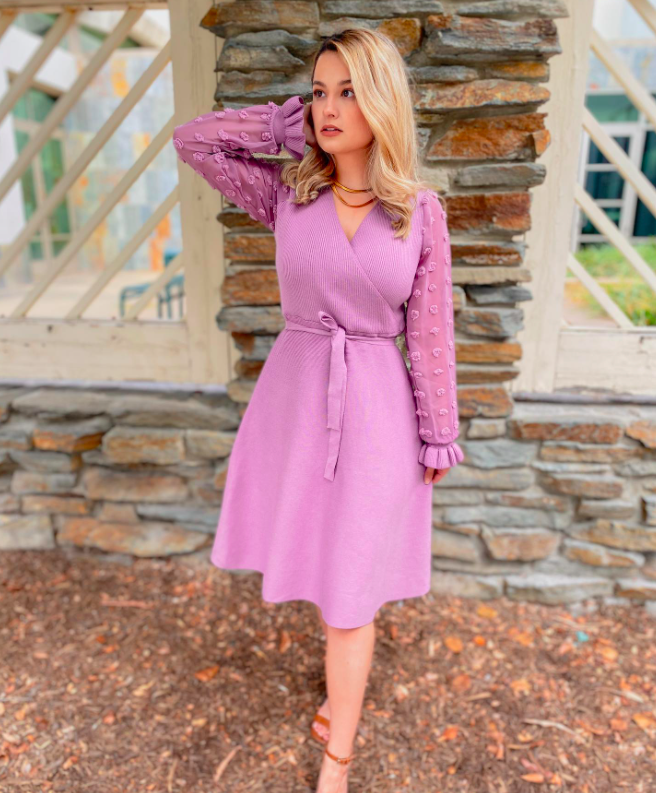 blogger wearing a lavender sweater wrap dress with bell sleeves, ruffled wrists, and lavender polka dots on the sleeves. The dress stops just below the knee and is one of the top-seliing dresses from the brand.