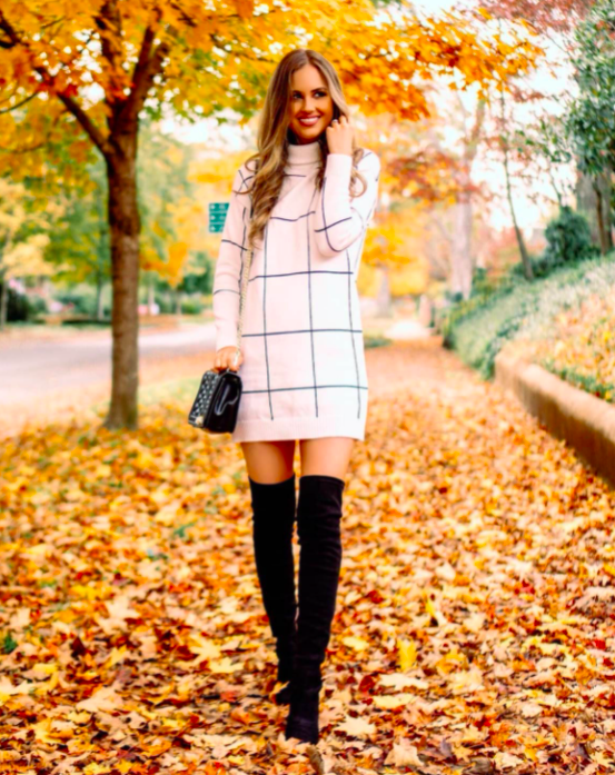 blogger wearing one of the Chicwish sweater dresses which has a white and back grid print and a short hemline. She's wearing it with boots and a black bag.