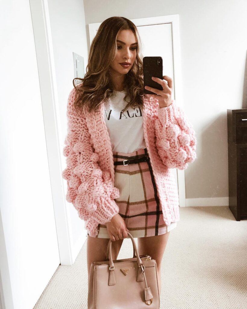 blogger wearing the pink bell sleeve chunky knit sweater with pom pom balls on the sleeves