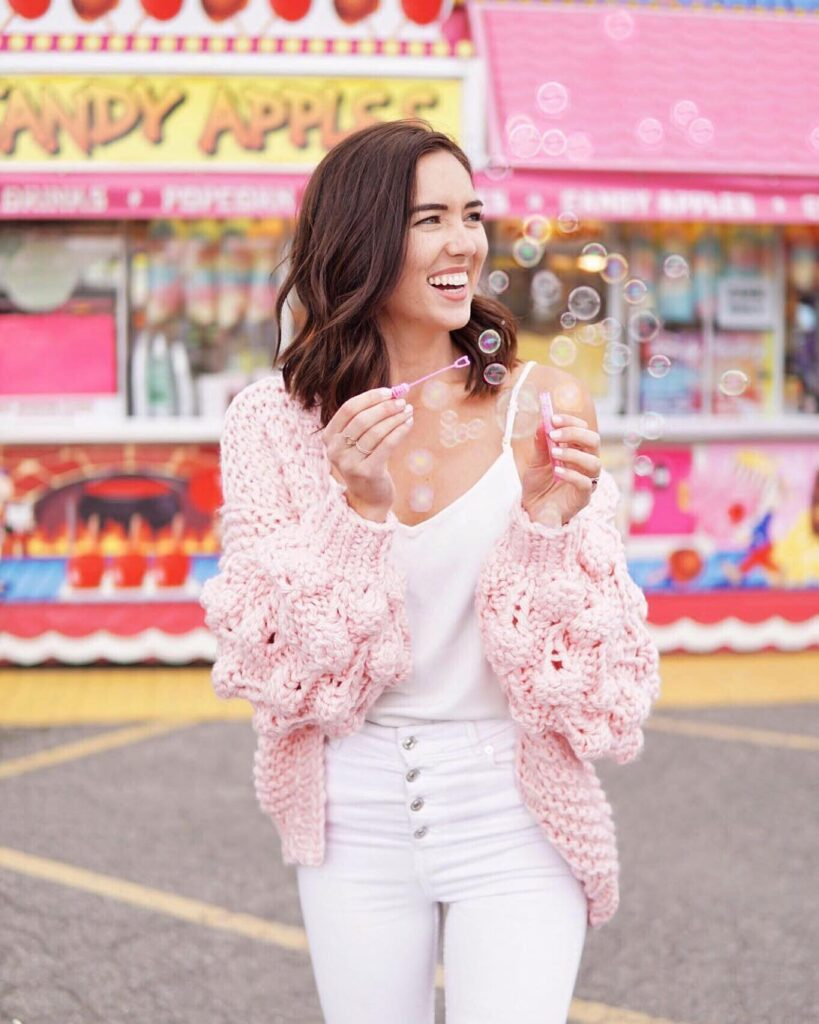 blogger wearing the pink bell sleeve chunky knit sweater with pom pom balls on the sleeves. the blogger is wearing it over a white tank top and jeans and standing in a carnival blowing bubbles