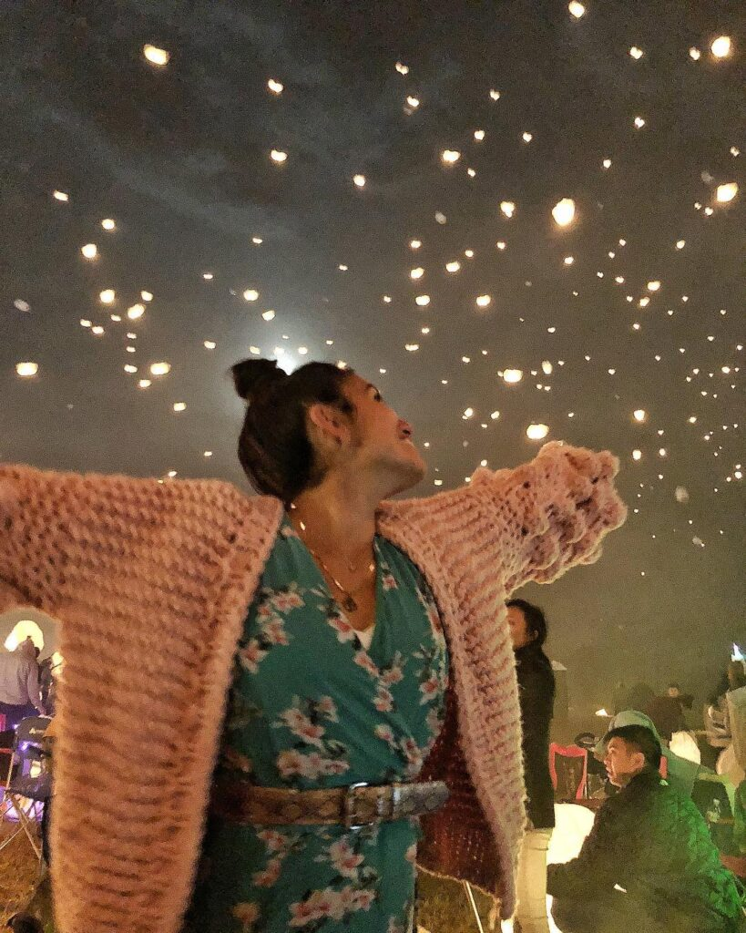 blogger wearing the pink bell sleeve chunky knit sweater with pom pom balls on the sleeves. the blogger is standing at a festival at night with lights in the sky