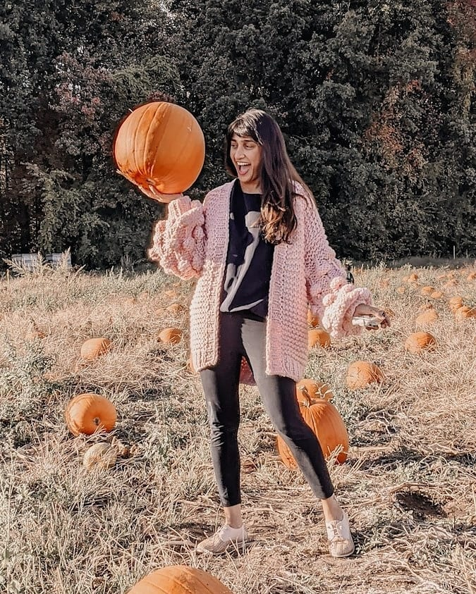 blogger wearing the pink bell sleeve chunky knit sweater with pom pom balls on the sleeves standing in a pumpkin patch