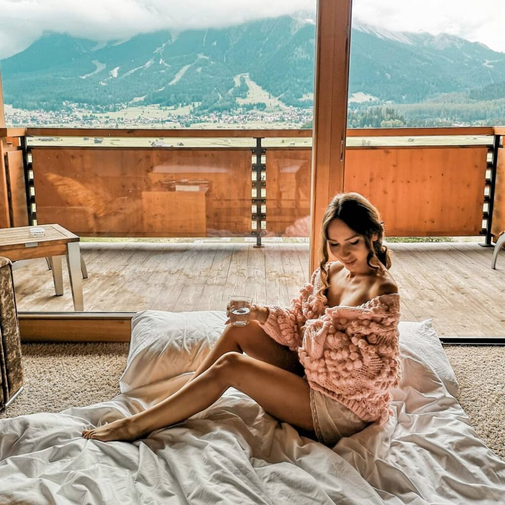 blogger wearing the pink bell sleeve chunky knit sweater with pom pom balls on the sleeves sitting in a resort in the mountains on a throw on the floor
