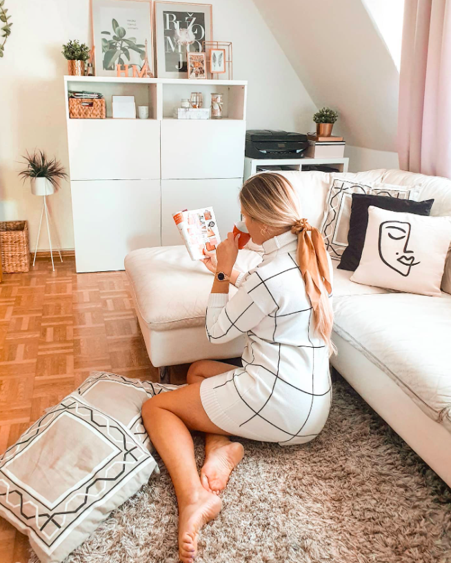 chicwish blogger wearing the white and black grid print dress while sitting on the floor reading a book as they lean against the couch
