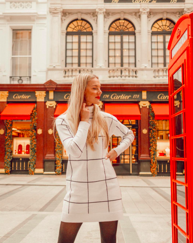 chicwish blogger wearing the white grid print turtleneck dress while standing in front of a storefront