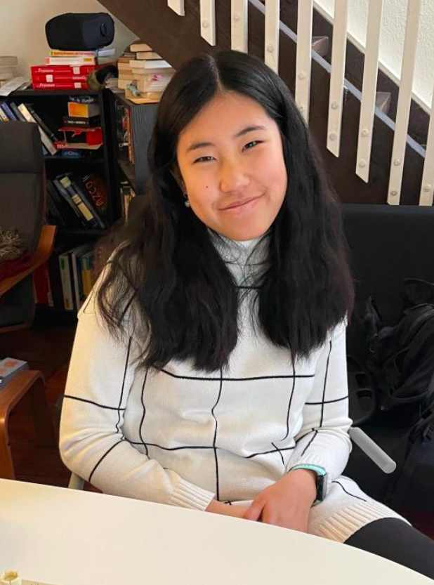 chicwish reviewer wearing the white and black turtleneck dress while sitting at their desk and smiling