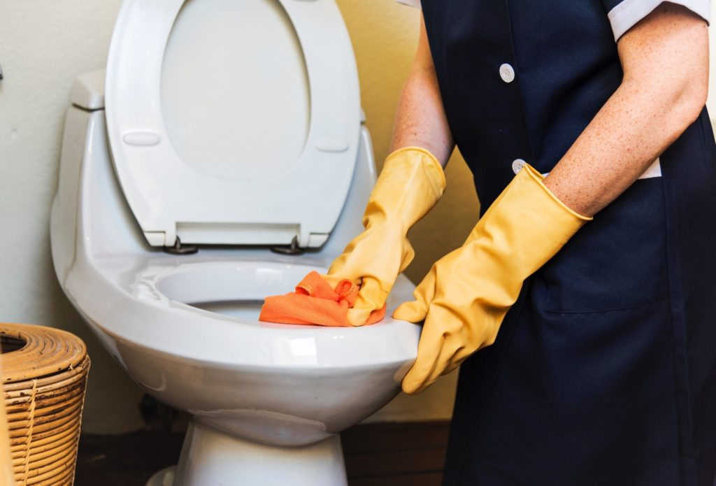Janitor cleaning a business toilet with a sponge