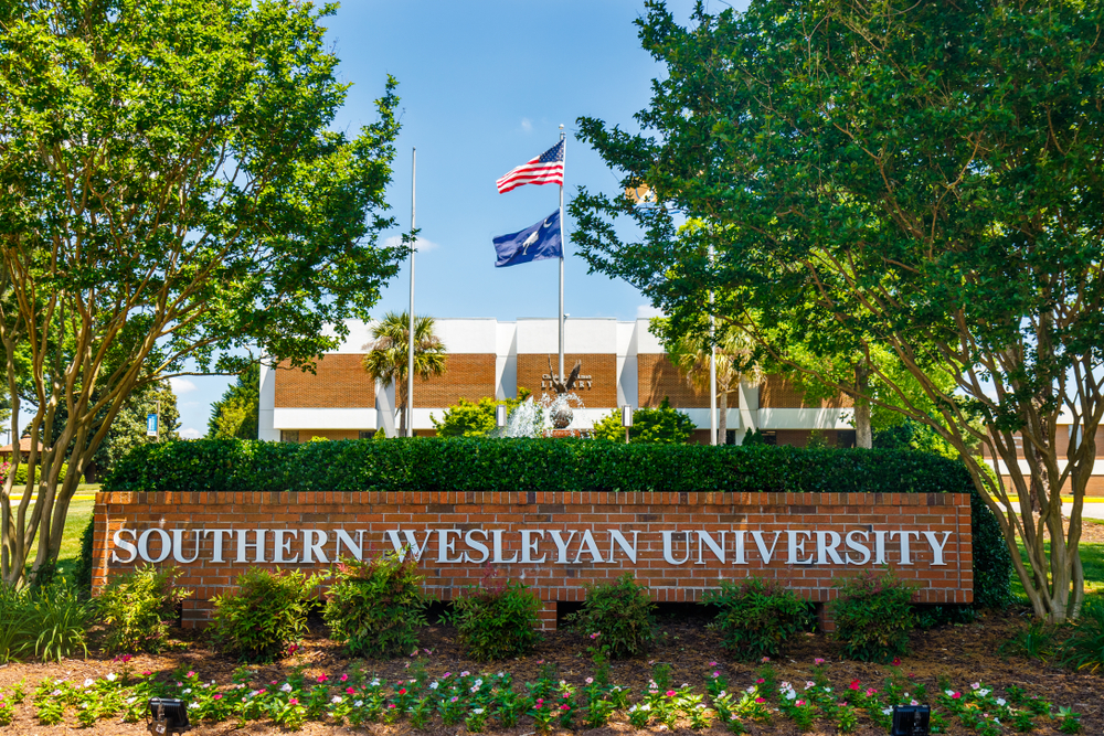 a sign for southern wesleyan university in front of a building on campus