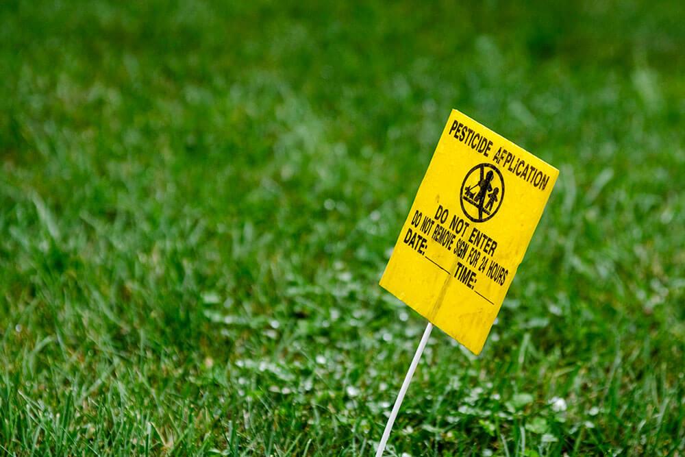 Landscape site with pesticide hazard sign