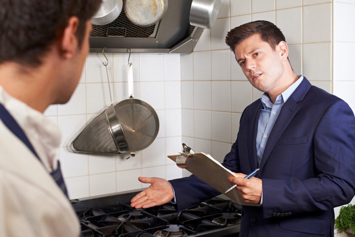Health inspector looking at kitchen commercial floor