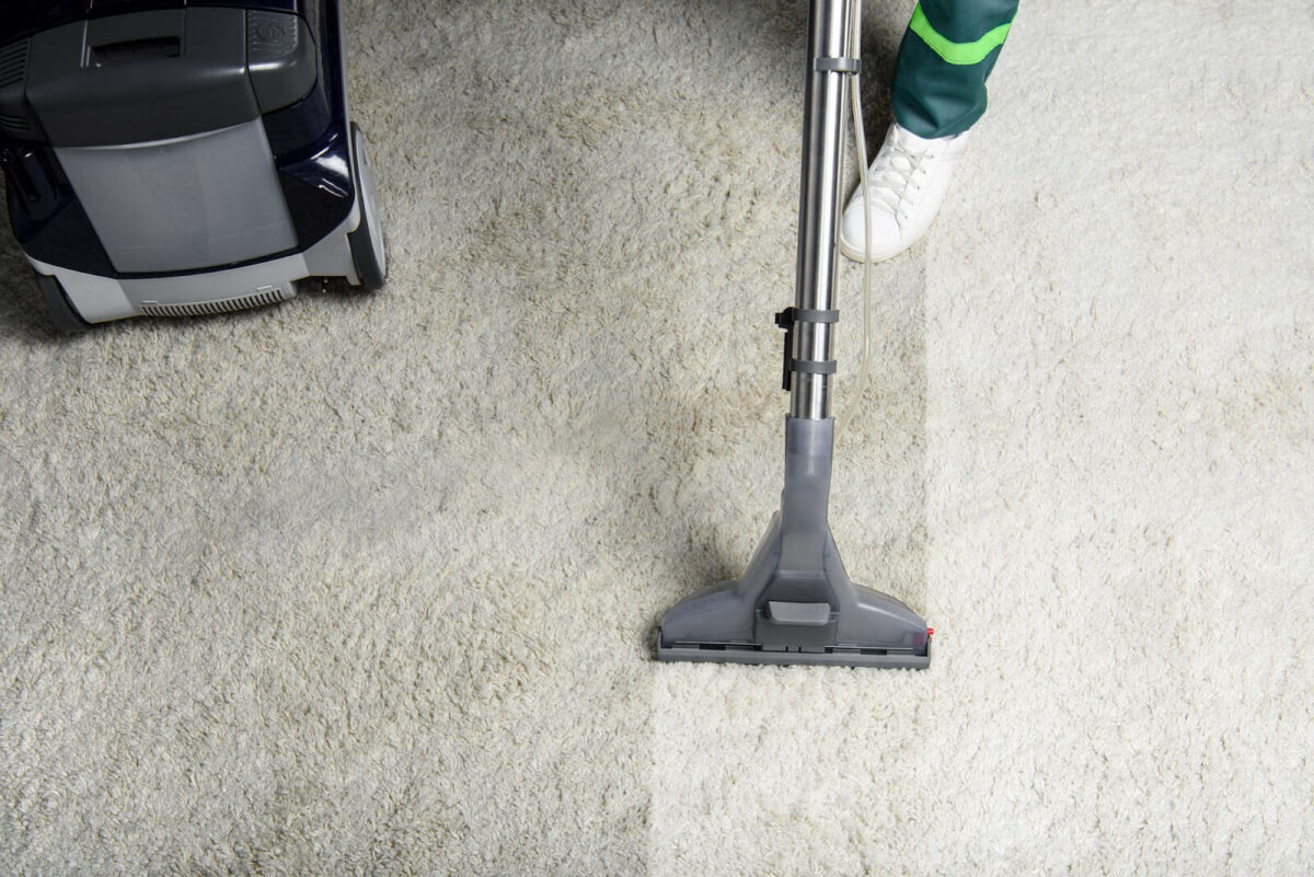 Carpet cleaner cleaning a white commercial carpet
