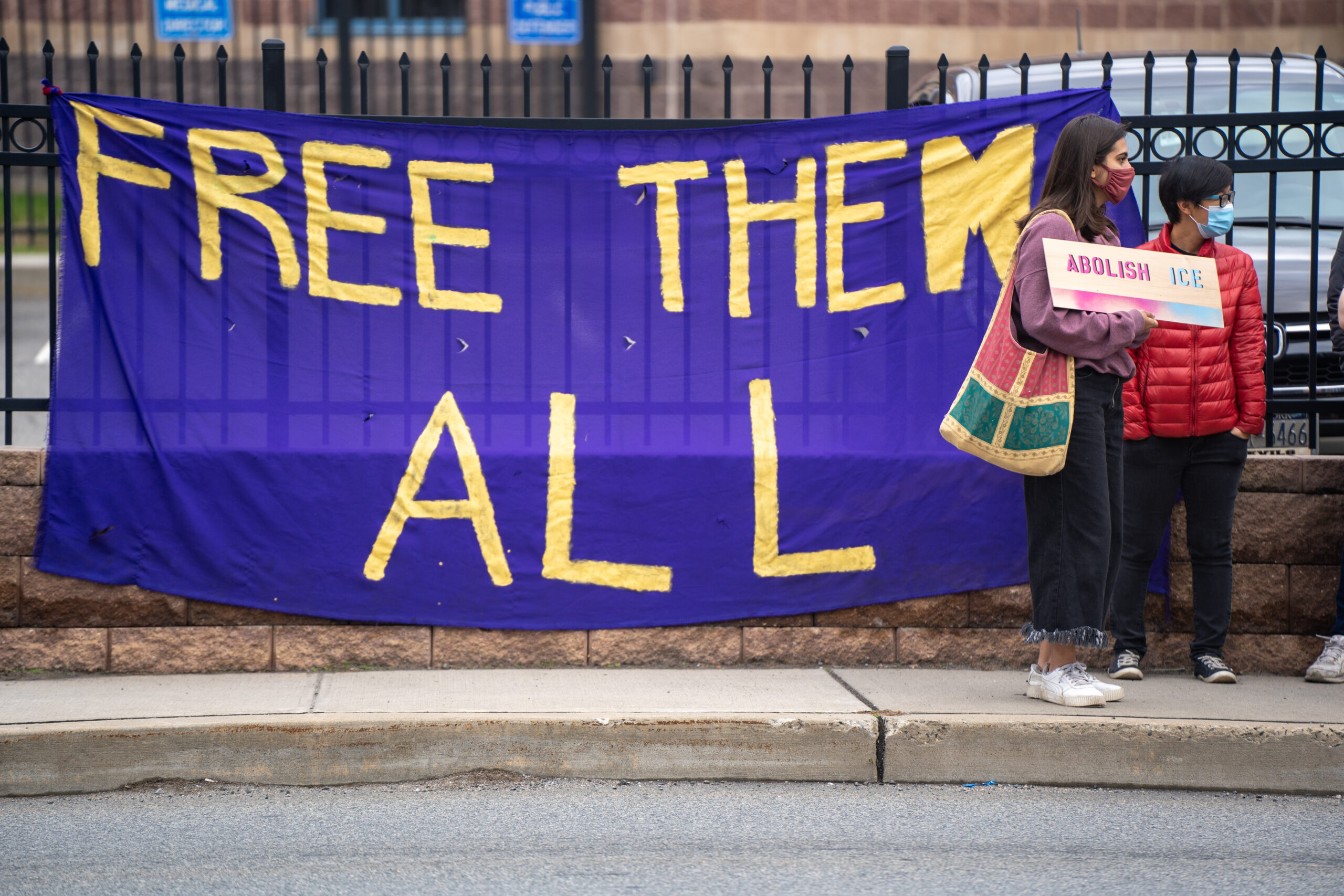 """Young woman and man standing in front of a banner that says """"Free Them All"""""""