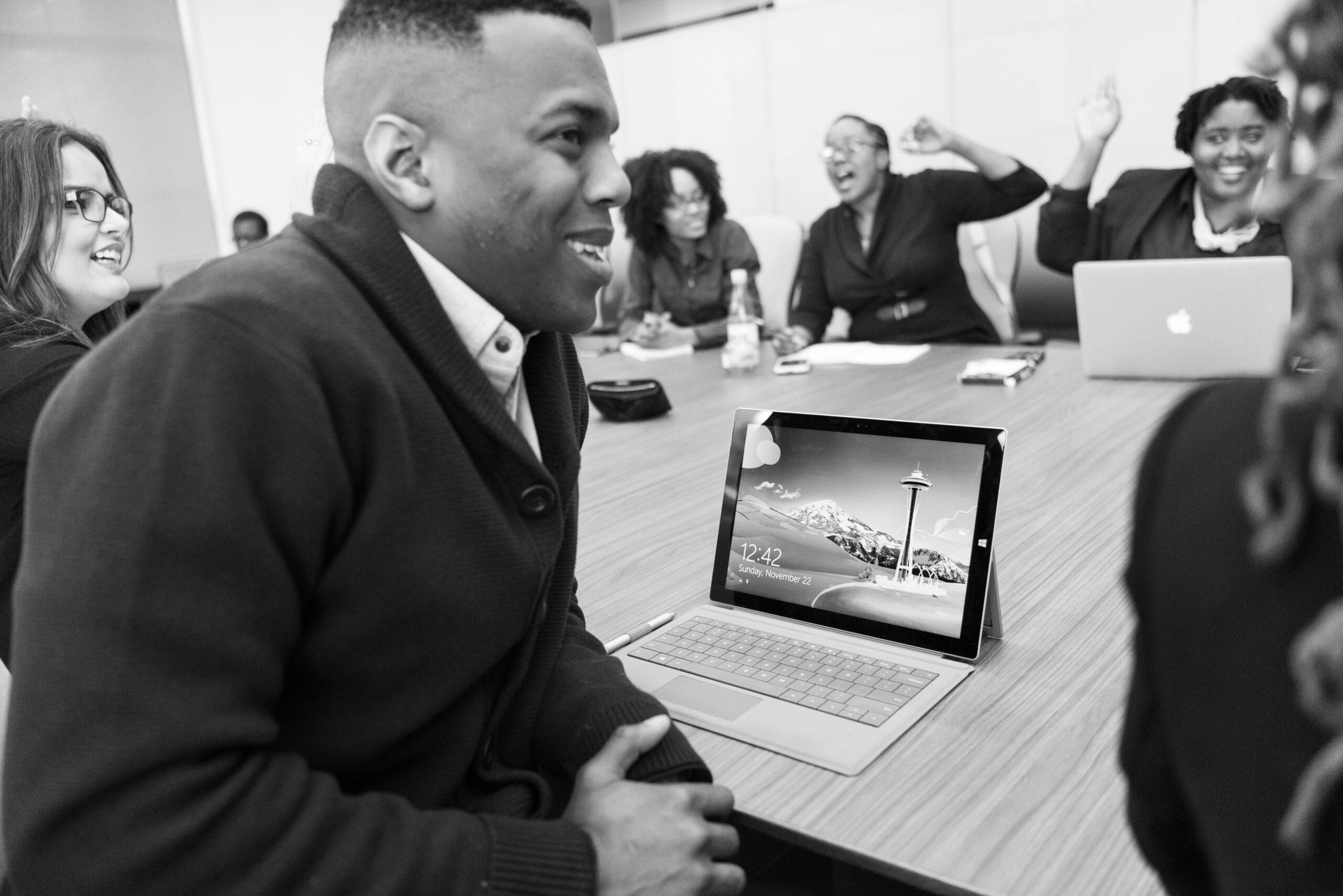 people laughing and cheering at a conference table