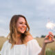 smiling woman holding sparkler and celebrating outdoor