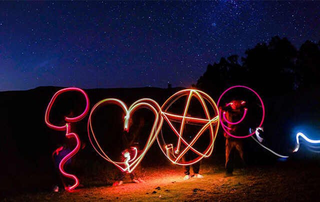 Four positive people standing in a field under a dark star lite sky using light to draw hearts, stars and smiling faces using slow exposure photography.